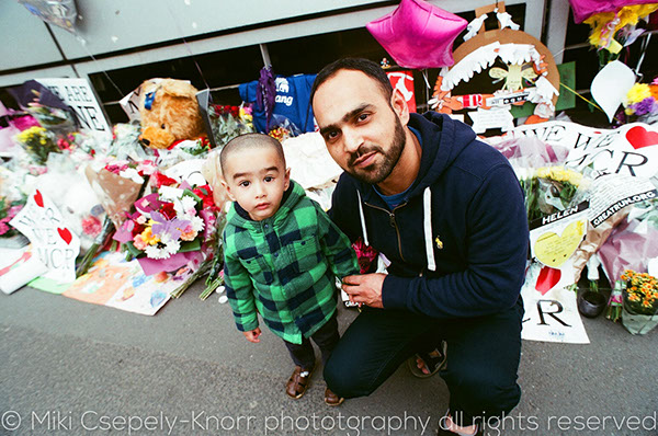 A colour image of a father and son in St Ann's Square, Manchester